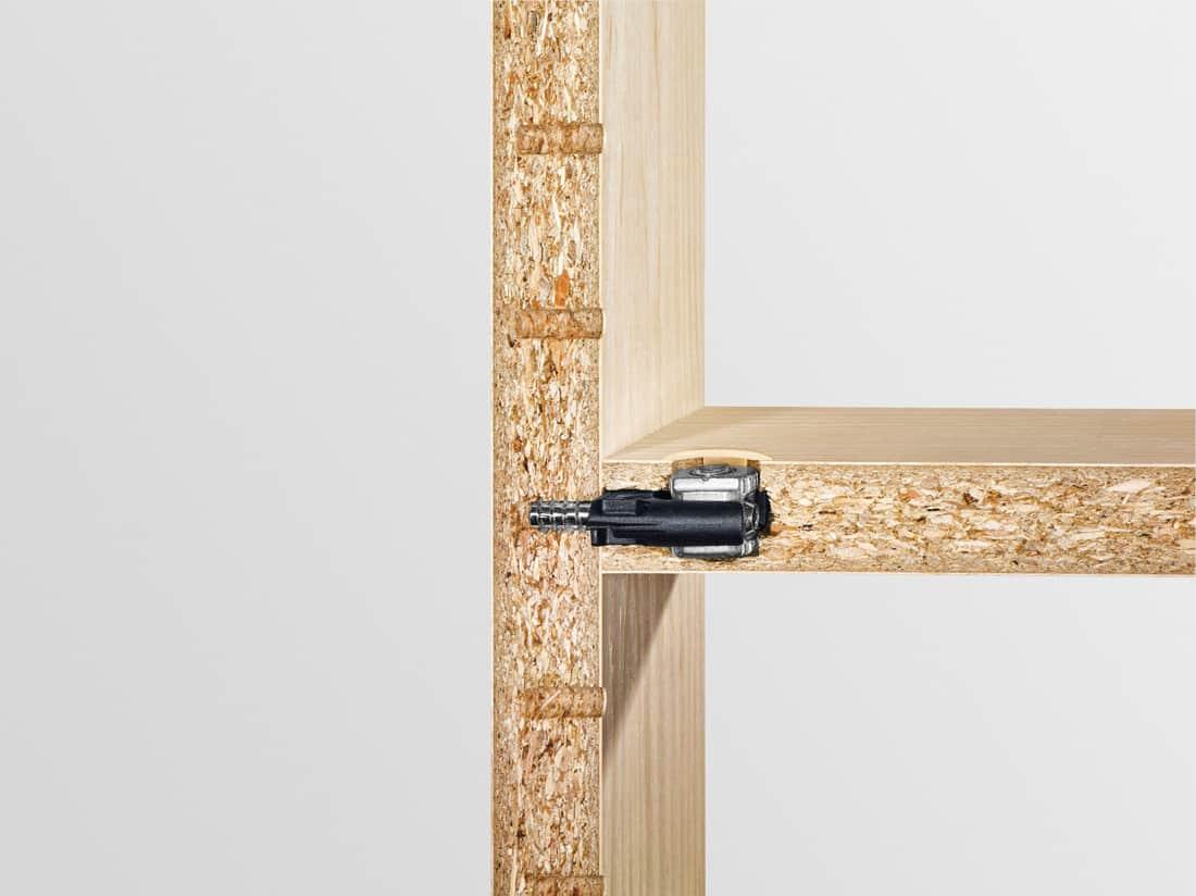 Łącznik kątowy DOMINO łączy rząd 32 otworów z podstawą konstrukcji. Okucie wkręca się bezpośrednio w 5-milimetrowy otwór w rzędzie, a podstawa konstrukcji montowana jest jak do tej pory, przy wykorzystaniu wyfrezowanego otworu DOMINO